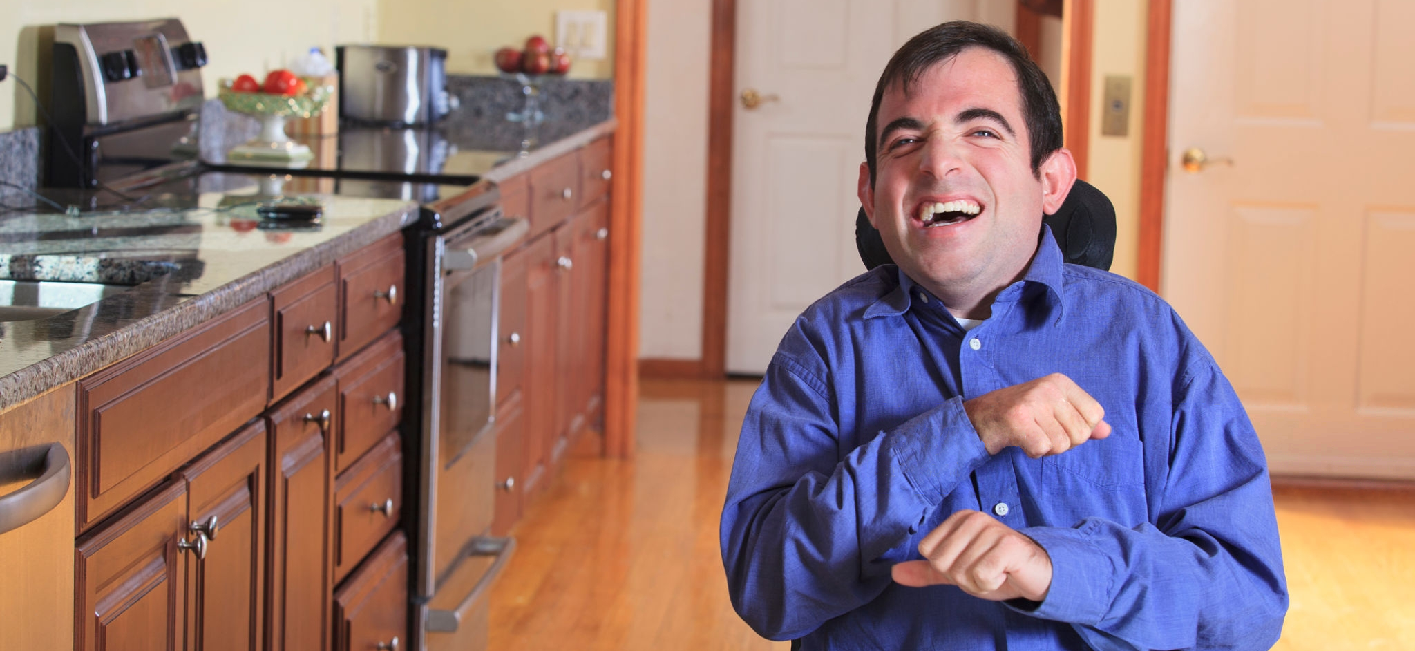 Smiling man in wheelchair in kitchen